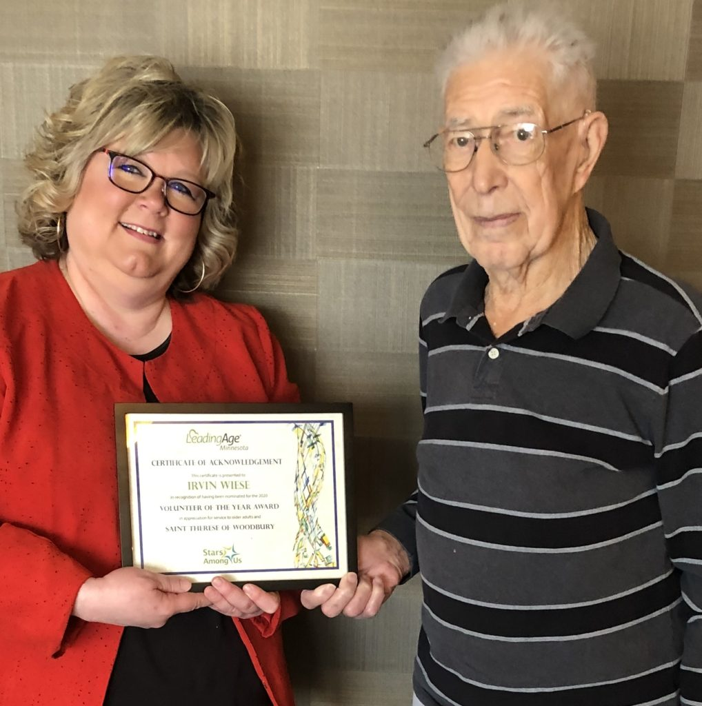 Saint Therese of Woodbury Marketing Director Caroline Cadalbert presents Irv Wiese with a Certificate of Acknowledgement in recognition for his efforts from LeadingAge Minnesota.
