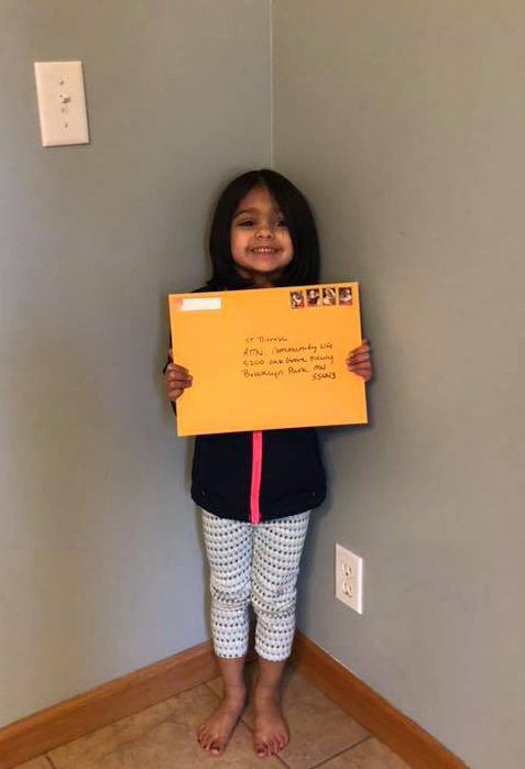 Little girl stands in living room holding large, yellow manila envelope addressed to Saint Therese at Oxbow Lake, Attention: Activities Team to boost residents' well-being.